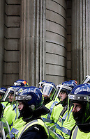 Police officers with riot helmets group together as thousands of protestors descended on the City of London ahead of the G20 summit of world leaders to express anger at the economic crisis, which many blame on the excesses of capitalism.