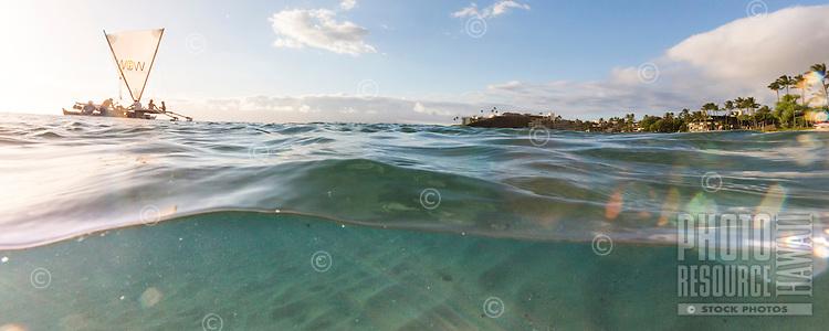 An over-and-under image of Ka'anapali Beach with a Hawaiian sailing canoe, Maui.