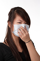 Montreal (qc) Canada -Dec 2010 - Model Released photo of a young asian adult woman wearing a mask to prevent spreading cold and flu