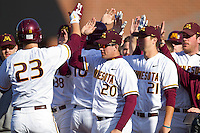 Nick O'Shea #23 of the Minnesota Golden Gophers is congratulated by his teammates after hitting a 2-run home run against the Towson Tigers at Gene Hooks Field on February 26, 2011 in Winston-Salem, North Carolina.  The Gophers defeated the Tigers 6-4.  Photo by Brian Westerholt / Four Seam Images