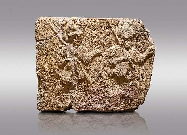 Picture & image of Hittite relief sculpted orthostat stone panel of Long Wall Limestone, Karkamıs, (Kargamıs), Carchemish (Karkemish), 900-700 B.C. . Anatolian Civilisations Museum, Ankara, Turkey.<br /> <br /> Two helmeted soldiers in short skirt carry shield on their backs and spear in their hands.<br /> <br /> On a gray background.