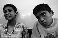 Baghdad, Iraq, April 5, 2003.Al Kindi hospital emergency ward, Firaz, 12, left is wounded in the abdomen, Youssef, 13, right, wounded to the feet and legs. Both are in deep psychological shock, Youssef unable to speak and shivering, several members of their family killed in front of their eyes in their home in Ubeidi. More than 70 US bombardment victims were admitted in less than 2 hours after a B52 carpet bombing on the Northern outskirts, about a fifth of these were military personel.
