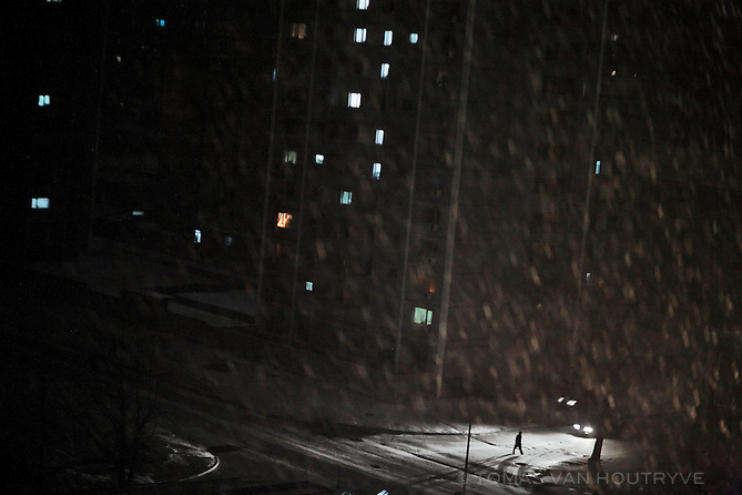 A man is illuminated by the headlights of a car while he walks through the snow at night in Pyongyang, North Korea (DPRK) on 25 February 2008.