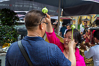 Bangkok, Thailand.  Worshipers Sprinkling Holy water on their Heads with a Lotus Blossom, Royal Grand Palace Compound.