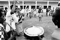 """Burundi. Karuzi Province. Karuzi. Young boys from the music group """"Karuzi's drums"""" play the drums and rehearse in the school yard the programm of their next musical performance .They all wear western clothes.  © 2000 Didier Ruef"""
