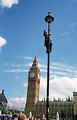 A young woman climbs a lamp post to string up a banner in Parliament Square during a Mayday action by Green activists and anti-capitalist demonstrators, organised by Reclaim the Streets and other groups.