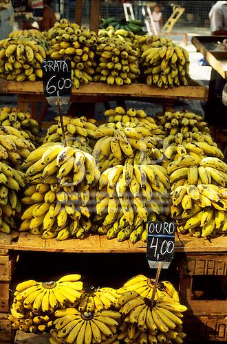Rio de Janeiro, Brazil. Street market stall selling piles of bunches of ripe yellow bananas.