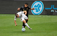 LOS ANGELES, CA - OCTOBER 25: Mohamed El-Munir #13 of LAFC battles Emiliano Insua #3 of the Los Angeles Galaxy during a game between Los Angeles Galaxy and Los Angeles FC at Banc of California Stadium on October 25, 2020 in Los Angeles, California.