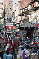 Kathmandu, Nepal.  Street Scene.  The structure holding the electric transformer and urban electrical wiring serves as a modern equivalent to the traditional Hindu shrine in the foreground.
