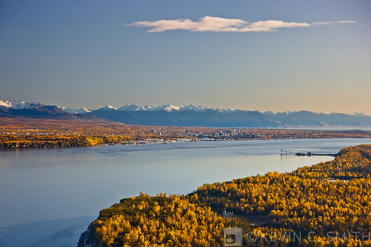 Aerial photo of loading dock and port at Point Mackenzie on the opposite side of Knik Arm from Anchorage with the anchorage ckyline and Chugach Mountains in the background, Fall, Southcentral Alaska, USA.
