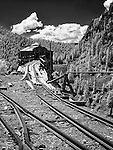 Black and white image of old Colorado mine with tracks