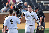 Will Craig (22) of the Wake Forest Demon Deacons knocks helmets with teammate Stuart Fairchild (4) after hitting a home run leading off the bottom of the 2nd inning against the Miami Hurricanes at Wake Forest Baseball Park on March 21, 2015 in Winston-Salem, North Carolina.  The Hurricanes defeated the Demon Deacons 12-7.  (Brian Westerholt/Four Seam Images)