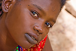 Fatimata Diallo comes from Eastern Burkina Faso, but has traveled to the capital, Ouagadougou, to visit relatives.  She bears the traditional facial scarring and black lip tattoos of the Fulani people.