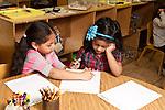 Education Preschool girl helping classmate with writing
