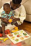 12 month old toddler boy with mother talking and looking at plastic play fruit and wooden puzzle pieces depicting fruit