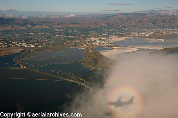 The shadow of a Boeing 737 inside a glory ring in the scattered fog on approach to runway 28R at San Francisco International Airport (SFO).  San Francisco Bay, the Dumbarton Bridge, Freemont, Milpitas and the Newark salt ponds are visible in the background.