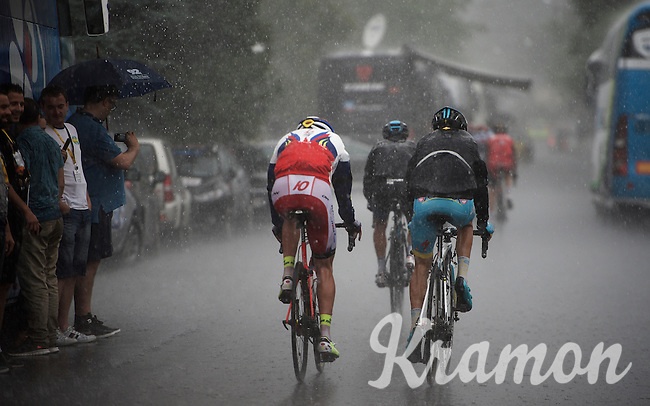 riders getting back to the teambus in a heavy rain storm after having descended from the finish in Pra Loupe<br /> <br /> stage 17: Digne-les-Bains - Pra Loup (161km)<br /> 2015 Tour de France