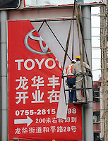 A billboard advertising a Toyota dealership is taken down in Shenzhen, China. Toyota, sold 709,000 cars in China last year, up 21 percent from the previous year but has been struggling to reassure a jittery public that it has turned a corner in dealing with safety issues that sparked a recall of 8.5 million vehicles..