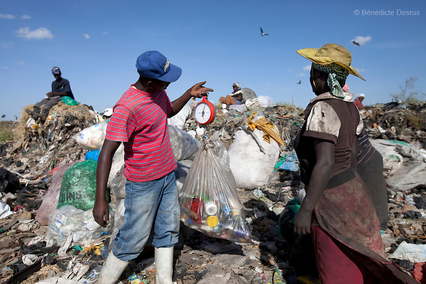 2013 - Dandora dumpsite, Nairobi, Kenya - A boy weighs recyclables on a scale in Dandora Dumpsite, one of the largest and most toxic in Africa. Located near slums in the east of the Kenyan capital Nairobi, the open dump site was created in 1975 and covers 30 acres. The site receives 2,000 tonnes of unfiltered garbage daily, including hazardous chemical and hospital wastes. It is a source of survival for many people living in the surrounding slums, however it also harms children and adults' health in the area and pollutes the Kenyan capital. Photo credit: Benedicte Desrus