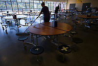 Custodians mop a cafeteria, Monday, October 5, 2020 at Clinton Elementary School in Clinton. Seats are marked to remind children to space out while having lunch. Check out nwaonline.com/2010010Daily/ for today's photo gallery. <br /> (NWA Democrat-Gazette/Charlie Kaijo)