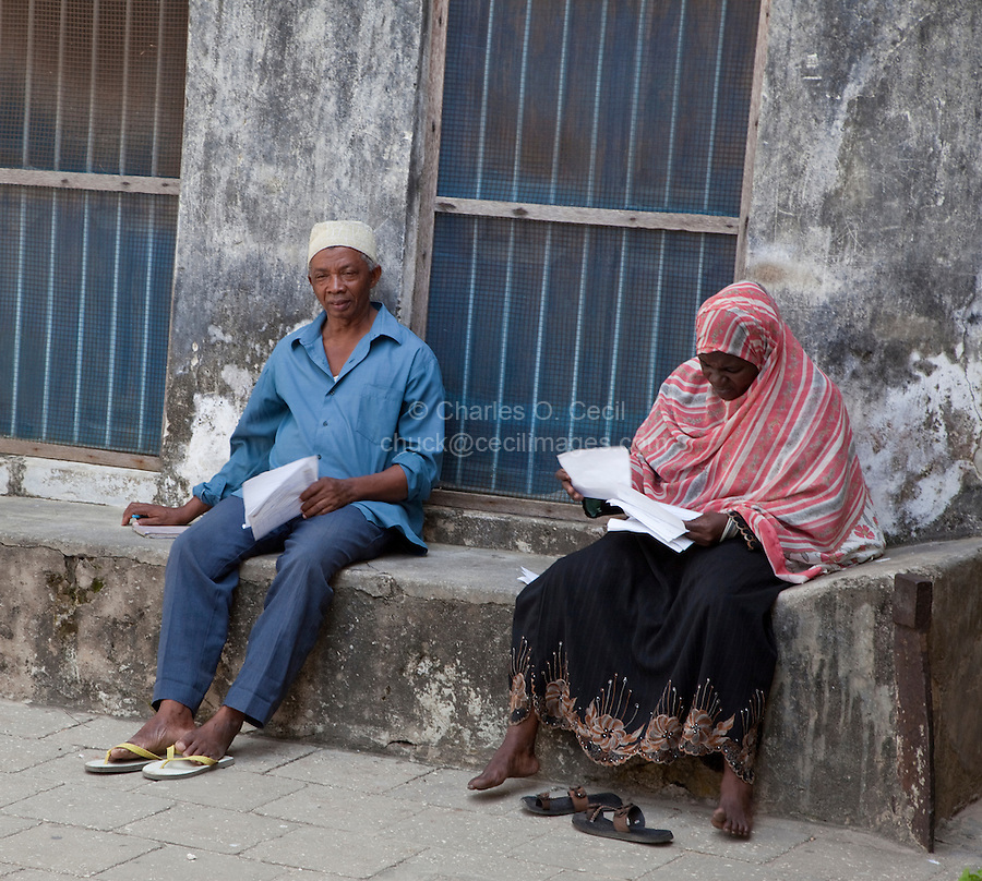 Stone Town, Zanzibar, Tanzania.  Sitting on a Baraza, a Stone Bench outside the door of many houses in Stone Town.