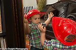 18 month old toddler boy looking at self in mirror wearing toy fire hat recognizing self