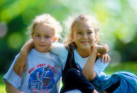 Two smiling eight year old girls sit cross-legged outdoors with their arms around each other in friendship. Set against a background of muted green foliage.