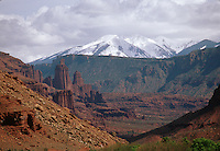 Rock formations and valley landscape with snow-capped mountains in the background, under a cloudy sky. Utah.