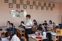 """Nagorno-Karabakh, also known as Artsakh, is a landlocked region in the South Caucasus. Stepanakert is the capital and the largest city of the Republic of Artsakh (better known as Nagorno-Karabakh). """" Hovhannes Tormanyan"""" Secondary School No 9. Classroom. 6th Grade. Pupils and their teacher during a mathematics class. On the wall, numerous frames with portraits of Armenian famous poets, the Artsakh flag and its coat of arms. The emblem of the Republic of Artsakh consists of an eagle above which is an ornamented crown. On the chest of the eagle is a shield with a panorama of a mountain range and under it a vertically set Flag of Artsakh. Over this are the two stone heads of """"Granny and Gramps""""  from the We Are Our Mountains monument in Stepanakert. The eagle's feet clutch various agricultural products including wheat and grapes. The outer rim is made up of a golden circular ribbon bearing inscription (""""Artsakh Republic of Mountainous Karabakh"""") in Armenian. On June 2, 1992, the self-proclaimed Republic of Artsakh adopted a flag derived from the flag of Armenia, with only a white pattern added. A white, five-toothed, stepped pattern was added to the flag, beginning at the two verges of the flag's right side and meeting at a point equal to one-third of the distance from that side. The white pattern symbolizes the current separation of Artsakh from Armenia proper and its aspiration for eventual union with """"the Motherland."""" This symbolizes the Armenian heritage, culture and population of the area, and represents Artsakh as a separated region of Armenia by the triangular shape and the zigzag cutting through the flag. The white pattern on the flag is also similar to the designs used on rugs, a symbol of national identity. Nagorno-Karabakh is a disputed territory, internationally recognized as part of Azerbaijan, but most of the region is governed by the Republic of Artsakh (formerly named Nagorno-Karabakh Republic), a de facto independent state with Armenian ethnic populati"""
