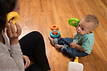 13 month old baby boy playing with mother pretend play using rings from toy as telephones