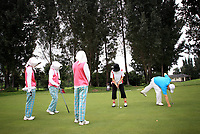 CHINA. Caddies and golfers prepare their shots at the Huatang International Golf Club in Beijing. 2009