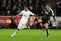 (L-R) Kyle Naughton of Swansea closely followed by Jamie Vardy of Leicester City during the Barclays Premier League match between Swansea City and Leicester City at the Liberty Stadium, Swansea on December 05 2015