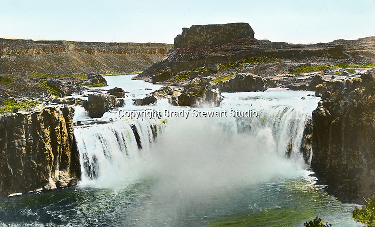 Twin Falls ID:  View of the Shoshone Falls.  Brady Stewart and three friends went to Idaho on a lark from 1909 thru early 1912.  As part of the Mondell Homestead Act, they received a grant of 160 acres north of the Snake River.  Brady Stewart photographed the adventures of farming along with the spectacular landscapes. To give family and friends a better feel for the adventure, he hand-color black and white negatives into full-color 3x4 lantern slides.  The Process:  He contacted a negative with another negative to create a positive slide.  He then selected a fine brush and colors and meticulously created full-color slides.