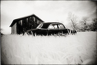 Old Car in tall grass in front of Barn<br />
