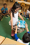 Education Preschool 3-4 year olds classroom scenes girl doing classroom job collecting picture books so that circle time can begin