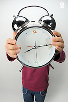 Girl (6-7) holding alarm clock over face (Licence this image exclusively with Getty: http://www.gettyimages.com/detail/sb10068346h-001 )