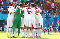 Mario Balotelli of Italy takes a moment to reflect as the Costa Rica team have a huddle before the start of the second half