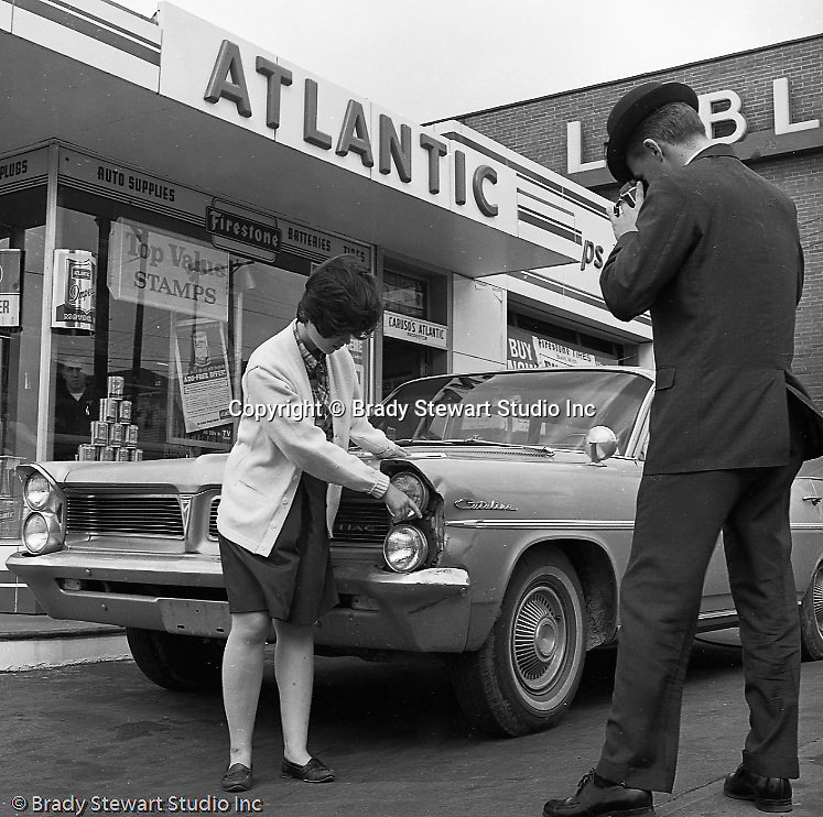 Pittsburgh PA:  View of an insurance adjuster taking a picture of the damage to the Stewart's 1964 Pontiac Catalina.  Cathy Stewart showing the damage to the insurance adjuster.  Another modeling assignment for a member of the Stewart family.
