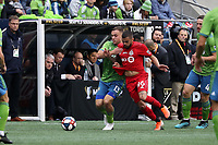 SEATTLE, WA - NOVEMBER 10: Jordan Morris #13 of the Seattle Sounders FC grapples with Auro Jr. #96 of Toronto FC while challenging for the ball during a game between Toronto FC and Seattle Sounders FC at CenturyLink Field on November 10, 2019 in Seattle, Washington.