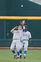 UCLA shortstop Pat Valaika (10) makes a catch in front of teammate Brenton Allen (23) against the North Carolina State Wolfpack during Game 8 of the 2013 Men's College World Series on June 18, 2013 at TD Ameritrade Park in Omaha, Nebraska. The Bruins defeated the Wolfpack 2-1, eliminating North Carolina State from the tournament. (Andrew Woolley/Four Seam Images)