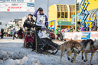 Jan Steves and team leave the ceremonial start line with an Iditarider at 4th Avenue and D street in downtown Anchorage, Alaska during the 2015 Iditarod race. Photo by Jim Kohl/IditarodPhotos.com