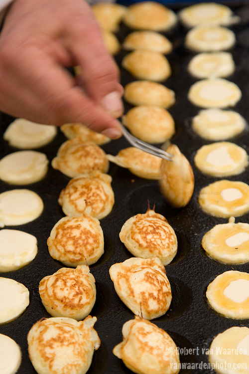 Poffertjes, small dutch pancakes, are being prepared for eating on the Albert Cuyp Market in Amsterdam.