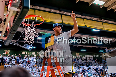 16 March 2019: University of Vermont Catamount Forward Isaiah Moll, a Freshman from Albany, NY, cuts himself a piece of net after a victory over the UMBC Retrievers in the America East Championship Game at Patrick Gymnasium in Burlington, Vermont. The Catamounts defeated the Retrievers 66-49, avenging their loss against the same team in last years' Championship Game. Mandatory Credit: Ed Wolfstein Photo *** RAW (NEF) Image File Available ***