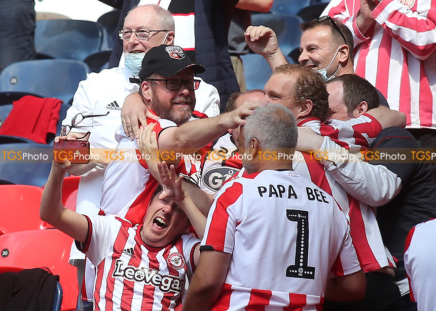 A Brentford fan tries to take a selfie to celebrate the Bees scoring their second goal, but he is mobbed by his mates instead during Brentford vs Swansea City, Sky Bet EFL Championship Play-Off Final Football at Wembley Stadium on 29th May 2021