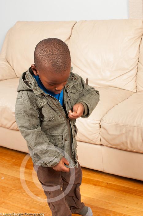 Boy, age 3, dressing self, pulling up zipper on coat