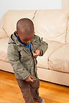 Boy, age 3, dressing self, pulling up zipper on coat