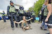 Pictured: A man sits infront of a line of police officers. Monday 31 August 2020<br /> Re: Around 70 South Wales Police officers executed a dispersal order at the site of an illegal rave party, where they confiscated sound gear used by the organisers in woods near the village of Banwen, in south Wales, UK.