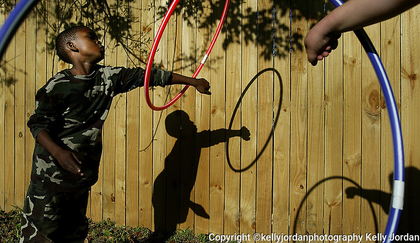 """Darius Butler, 7, of Daytona Beach, left, plays with a hula hoop with his fellow student Christine Gould, 8, hand, as they enjoy the warm weather during their outside activity time at Mary's Learning Center in Daytona Beach Thursday March 11, 2004. Darius ssays, """"hula hooping is one of my favorite things to do, I like to switch arms which I just learned"""", as he takes a break from his twirling.(Kelly Jordan)..**FOR STAND ALONE FEECH**"""