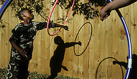 "Darius Butler, 7, of Daytona Beach, left, plays with a hula hoop with his fellow student Christine Gould, 8, hand, as they enjoy the warm weather during their outside activity time at Mary's Learning Center in Daytona Beach Thursday March 11, 2004. Darius ssays, ""hula hooping is one of my favorite things to do, I like to switch arms which I just learned"", as he takes a break from his twirling.(Kelly Jordan)..**FOR STAND ALONE FEECH**"