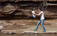 """Tristan Sebring, 1, gets a ride from his mother, Erica Langmade of Boone while the two cross a path of step stones over a creek Tuesday afternoon at Ledges State Park near Boone.  The two were making the most of this spring's warmest day, as temperatures went well over 70 degrees.  """"It's beautiful!"""" Langmade exclaimed."""